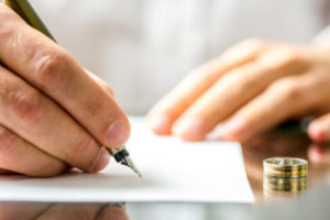 Closeup of a man signing  divorce papers.